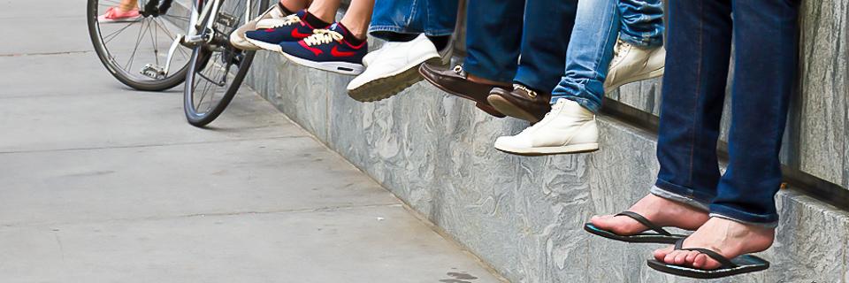 Hängende Füße von Jugendlichen auf Steinbarriere